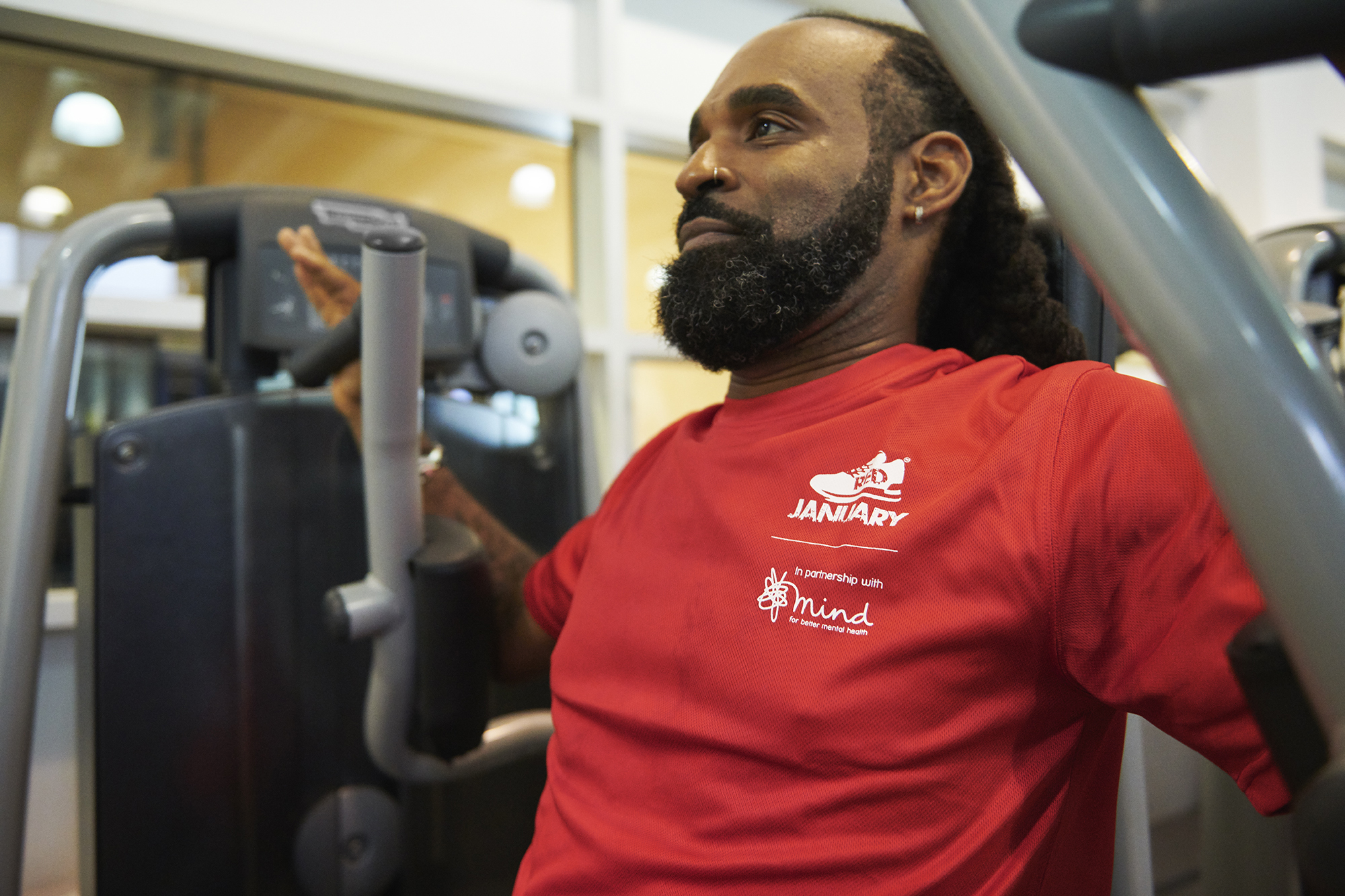 Man using gym equipment wearing RED January t-shirt