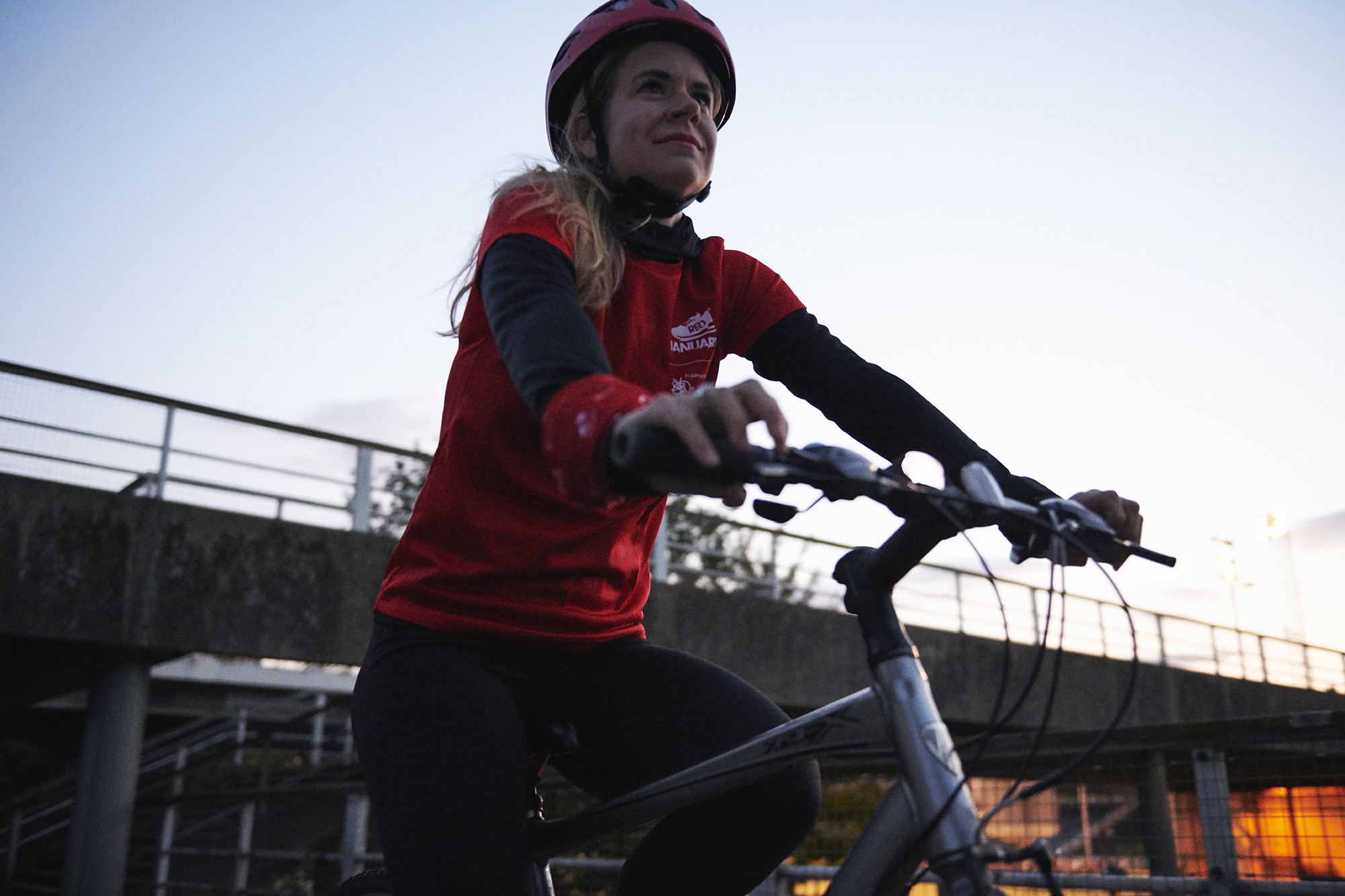 Woman cycling across a bridge for RED January